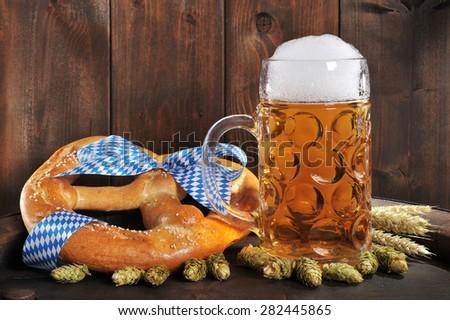 original bavarian Oktoberfest big soft pretzel with beer mug, hops and wheat on old beer barrel - stock photo