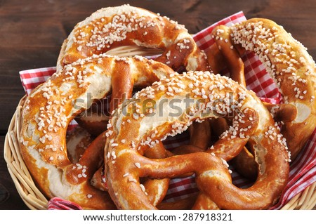 original bavarian Oktoberfest salted soft pretzels in a basket from Germany on wooden board - stock photo