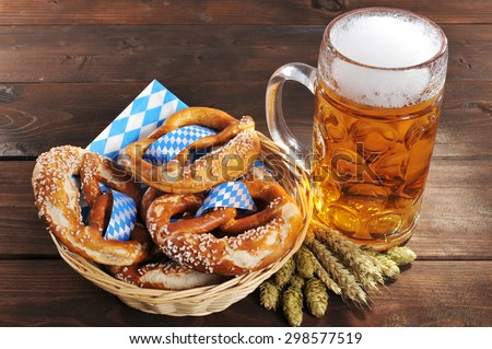 original bavarian Oktoberfest salted soft pretzels in a basket with beer from Germany on wooden board