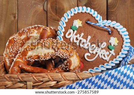 original bavarian salted soft pretzels Oktoberfest gingerbread heart in front of wooden board - stock photo