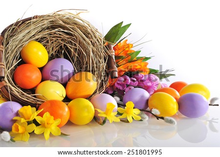 original easter eggs in yellow, violet and orange with flowers and easter nest