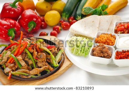 original fajita sizzling smoking hot served on iron plate and fresh vegetables on background - stock photo