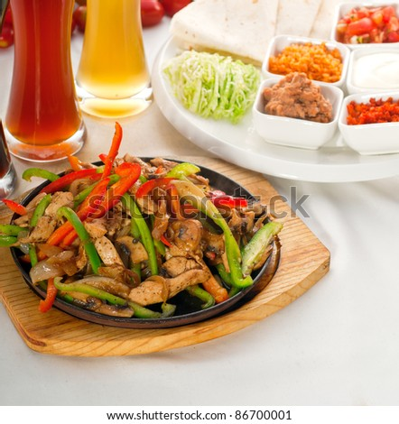 original fajita sizzling smoking hot served on iron plate ,with selection of beer and fresh vegetables on background - stock photo