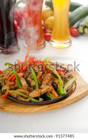 original fajita sizzling smoking hot served on iron plate ,with selection of beer and fresh vegetables on background ,