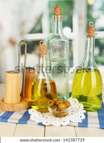 Original glass bottles with salad dressing on wooden table on window background