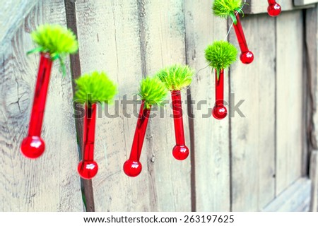 Original hanging red glass flower vases-tubes on wooden background in botanic garden. Outdoors. - stock photo