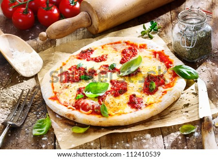 Original italian Pizza Margherita with cheese and tomato sauce on an old wooden board. For parlour concepts. - stock photo