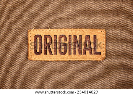 Original Leather Label Tag on cotton fabric texture background. - stock photo