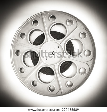 Original old big movie reel for 35 mm cinema  projector loaded with film in vintage effect black and white - stock photo