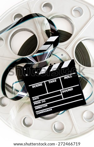 Original old big movie reel for 35 mm cinema projector with clapper board and unrolled film, vertical on neutral background - stock photo