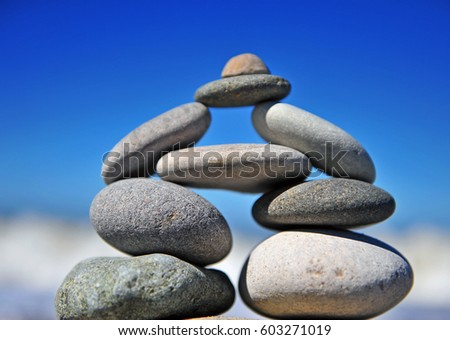Original stones pyramid standing on the beach with blue sky on background. Summer natural scene