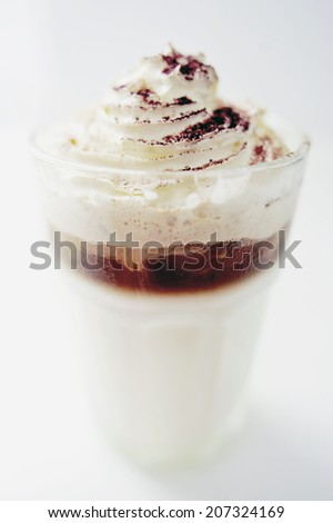 Original styled cool iced coffee with milk whipped cream and cocoa powder topping on white background - stock photo