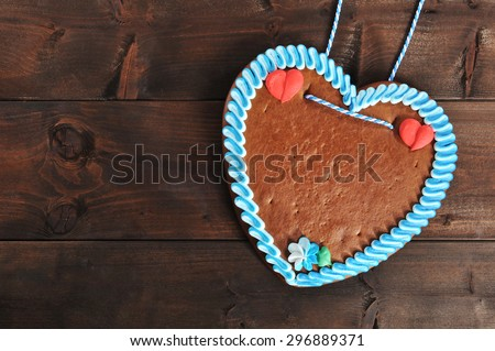 original unlabeled bavarian gingerbread heart from Germany on old weathered wooden board - stock photo