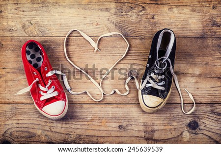Original Valentine's Day love concept with red and black sneakers. Studio shot on a wooden floor background. - stock photo