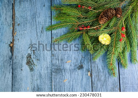 Originally decorated Christmas background with green branches, lemon and red berries on light blue wooden surface - stock photo