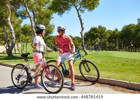 Orihuela, Spain - June 17, 2016: A pair of cyclists, boy and girl, going near beautiful golf courses on bicycles in helmets