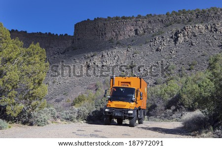ORILLA VERDE RECREATIONAL AREA, NEW MEXICO, USA - April 16: Custom orange RV truck driving on dirt road on April 16, 2014 at Orilla Verde Recreational Area, New Mexico, USA.