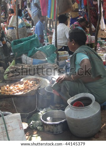 ORISSA INDIA - NOV 10 : Woman prepares fried food for snacks at  a  weekly market on November 10, 2009  in Orissa, India. - stock photo
