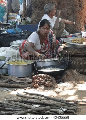 ORISSA, INDIA - NOVEMBER 10 : Woman prepares fried food for snacks at  a  weekly market November 10, 2009 in Orissa, India. - stock photo