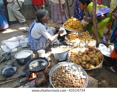 ORISSA, INDIA - NOVEMBER 10: Woman prepares fried food for snacks at a weekly market on November 10, 2009 in Orissa, India. - stock photo