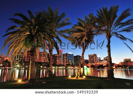 Orlando downtown skyline panorama over Lake Eola at night with urban skyscrapers, tropic palm tree and clear sky. - stock photo