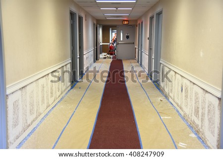 Orlando, FL - April 04-2016: Renovating and repainting office building hallway walls using spray method and taping to provide protection of carpet