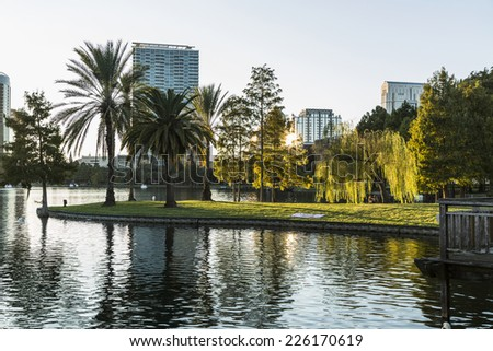 Orlando Lake Eola in the afternoon with urban skyscrapers before sunset - stock photo