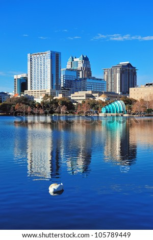 Orlando Lake Eola in the morning with a group of urban skyscrapers and clear blue sky with swan sleeping in water. - stock photo