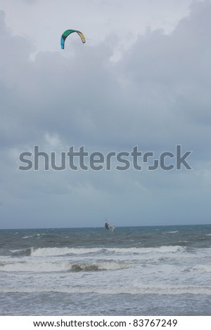 ORMOND BEACH, FL - AUGUST 25:  An unidentified kite-boarder is lifted in the air as Hurricane Irene passes off the coast on August 25, 2011 in Ormond Beach, Florida. - stock photo
