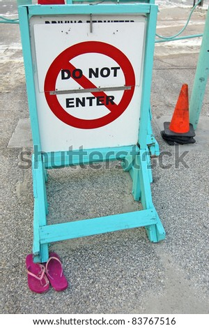 ORMOND BEACH, FL - AUGUST 25: Flip flops are secured under a warning sign in the storm surge as Hurricane Irene passes off the coast on August 25, 2011 in Ormond Beach, Florida . - stock photo