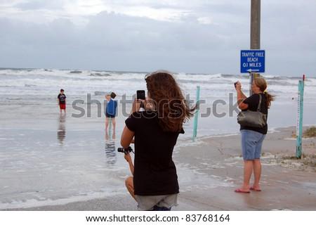 ORMOND BEACH, FL - AUGUST 25: Residents take photos as the ocean breaches the beach driving ramp as Hurricane Irene passes off the coast on August 25, 2011 in Ormond Beach, Florida . - stock photo