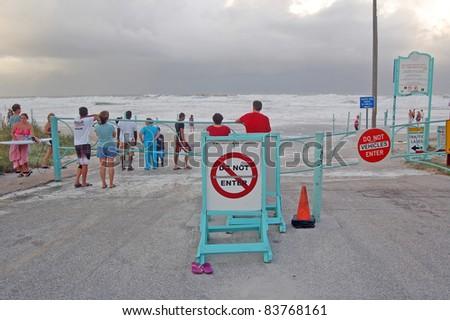ORMOND BEACH, FL - AUGUST 25: Residents watch the ocean breach the beach driving ramp as Hurricane Irene passes off the coast on August 25, 2011 in Ormond Beach, Florida . - stock photo