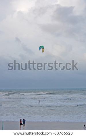 ORMOND BEACH, FL - AUGUST 25:  Spectators take photos of an unidentified kite-boarder as Hurricane Irene passes off the coast on August 25, 2011, in Ormond Beach, Florida. - stock photo