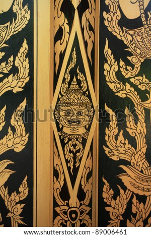 Ornament: detailed painting of gold hanuman on temple door