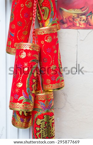 Ornament of paper firecrackers hanging on the wall. Often used during Chinese New Year. Chinese text meaning: amass fortunes and good fortune. - stock photo