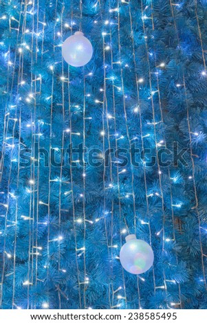 Ornamental electric light ball hanging on Cristmas tree - stock photo
