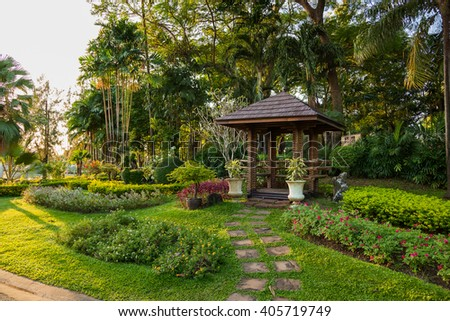 Ornamental plants and trees in the garden. Palmtrees, flowers and wooden pavilions. Bangkok, Thailand.