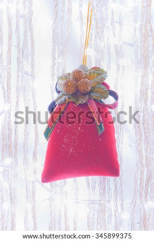 Ornamental red velvet bag on Christmas tree - stock photo