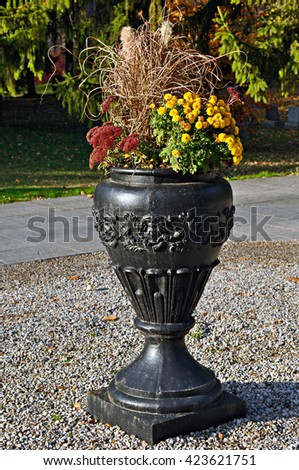 Ornamental vase with flowers in autumn - stock photo