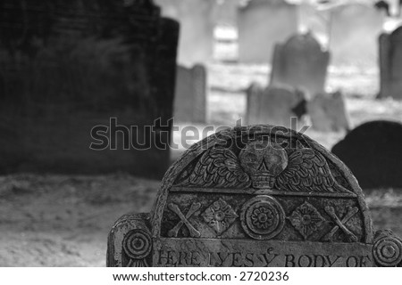 ornate ancient grave stone detail showing winged skull with cross bones and flowers - stock photo