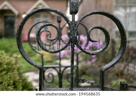 Ornate antique wrought iron detail on fence in front of house - stock photo