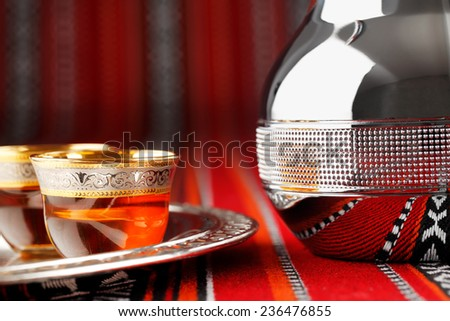 Ornate arabian tea cups and a dallah are placed on traditional red fabric from the gulf region. - stock photo