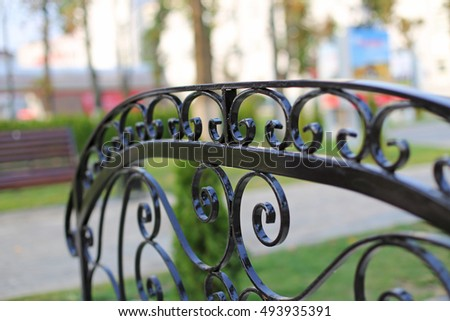 Ornate black forged metal railing element close up