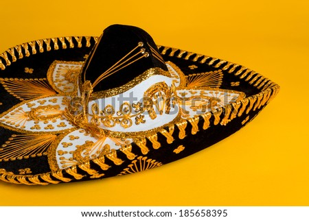 Ornate black, gold and white Mexican sombrero on a bright yellow background - stock photo