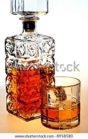 Ornate bottle and glass of whiskey and ice against white background. - stock photo