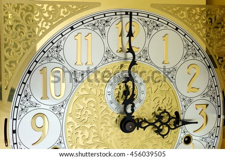 ornate brass engraved grandfather clock face with arabic numerals and hands on three o'clock  - stock photo