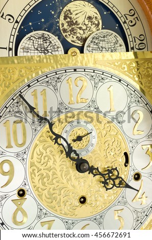 ornate brass engraved grandfather clock face with arabic numerals and moon phase dial - stock photo