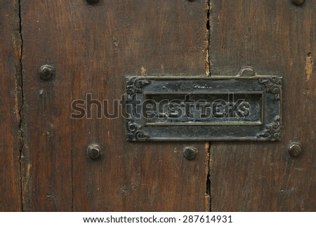 Ornate brass letterbox with inscription Letters on brown wooden background. - stock photo
