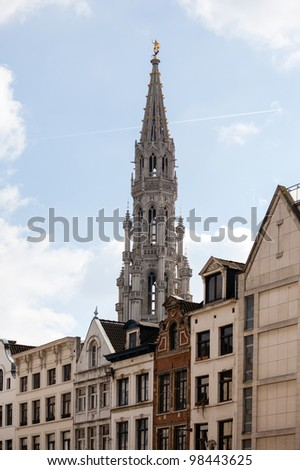 Ornate Brussels Town Hall in Grand Place over old and new buildings - stock photo