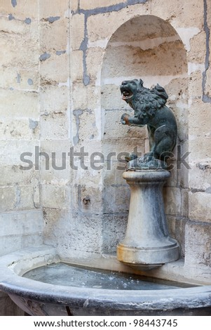 Ornate Brussels Town Hall in Grand Place with detail of water fountain carved with lion statue - stock photo